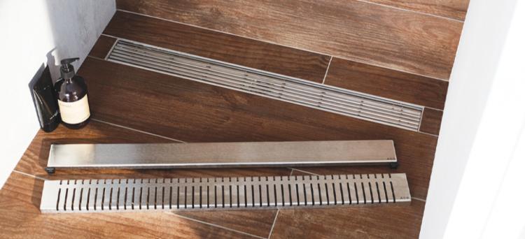 Canal de chuveiro SHOWERDRAIN-C instalada em um piso com efeito de madeira