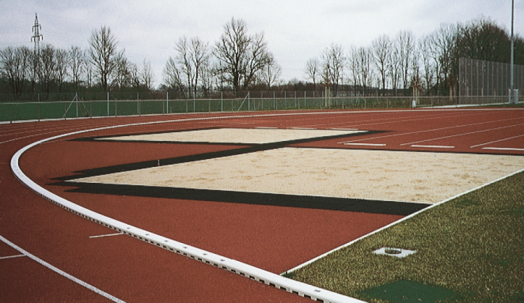 Canal LW125 con reja de plastico y arenero en una pista de atletismo