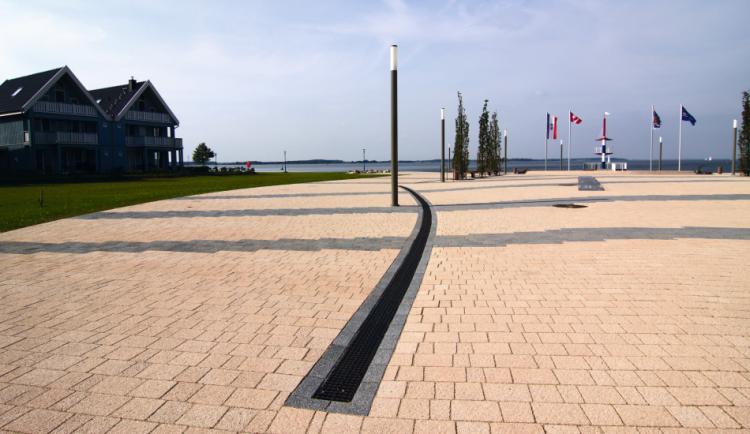 Canal MULTILINE V100 com grelha passarela em fundição no passeio ao lado de um lago
