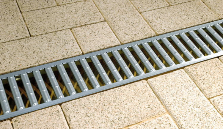 Canal SELF 100 con reja pasarela de acero galvanizado en una zona con adoquines