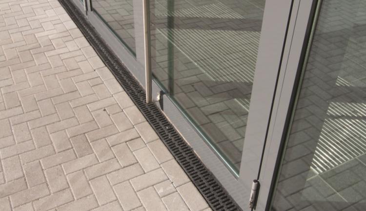 XTRADRAIN 100 com grelha pasarela em composite na frente da porta de um prédio