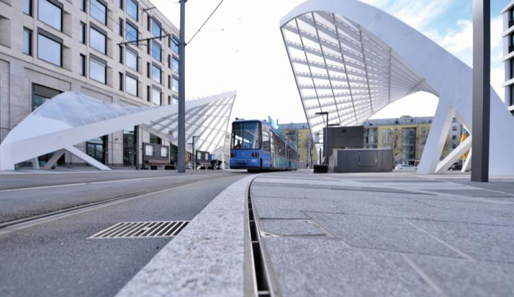 Reja brickslot-L para el canal MULTIDRAIN/MULTILINE en una calle al lado de un tranvia
